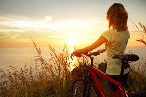 Eine Frau steht mit Fahrrad an der Küste und schaut in den Sonnenuntergang
