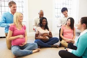 3 Paare und eine Hebamme beim Geburtsvorbereitungskurs