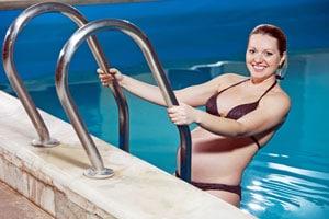 Schwangere Frau steigt im Schwimmbad aus dem Wasser