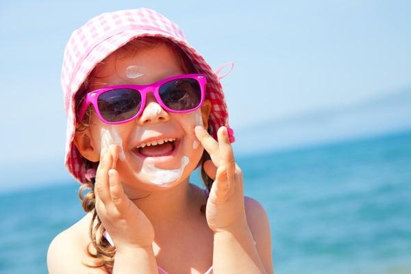 Mädchen cremt sich am Strand in der Sonne mit Sonnencreme ein
