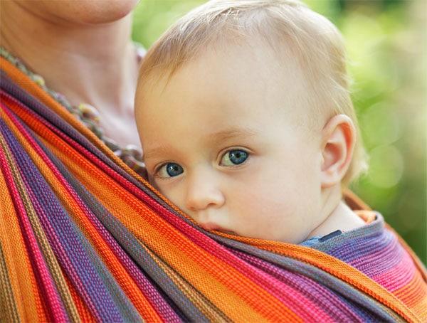 Baby in einem bunten Tragetuch vorne von der Mutter getragen