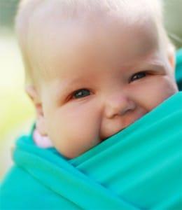 Baby in einem elastischen Tragetuch  vor der Brust der Mutter getragen