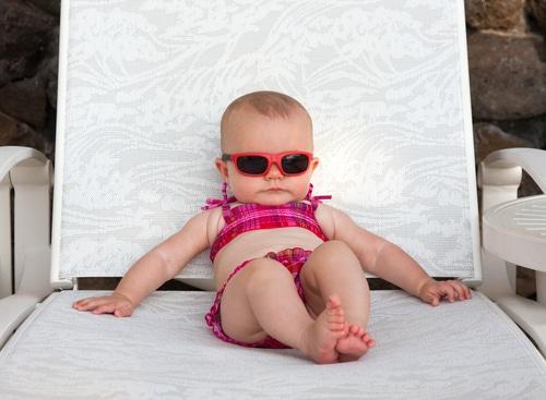 Baby mit Sonnenbrille liegt auf einer Sonnenliege