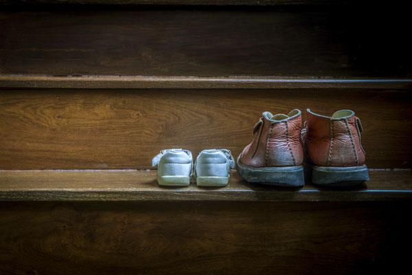 Kleine und große Schuhe stehen auf der Treppe