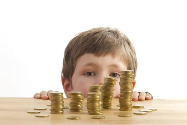 Kind sieht Geldstapel auf dem Tisch