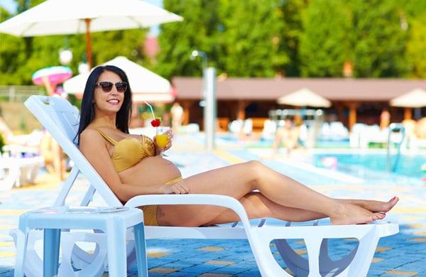 Schwangere Frau auf Sonnenliege am Pool