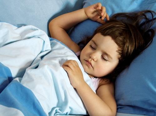 Kind schläft unter einer Bettdecke