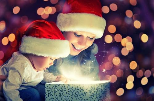 Baby und Mutter öffnen ein Weihnachtsgeschenk