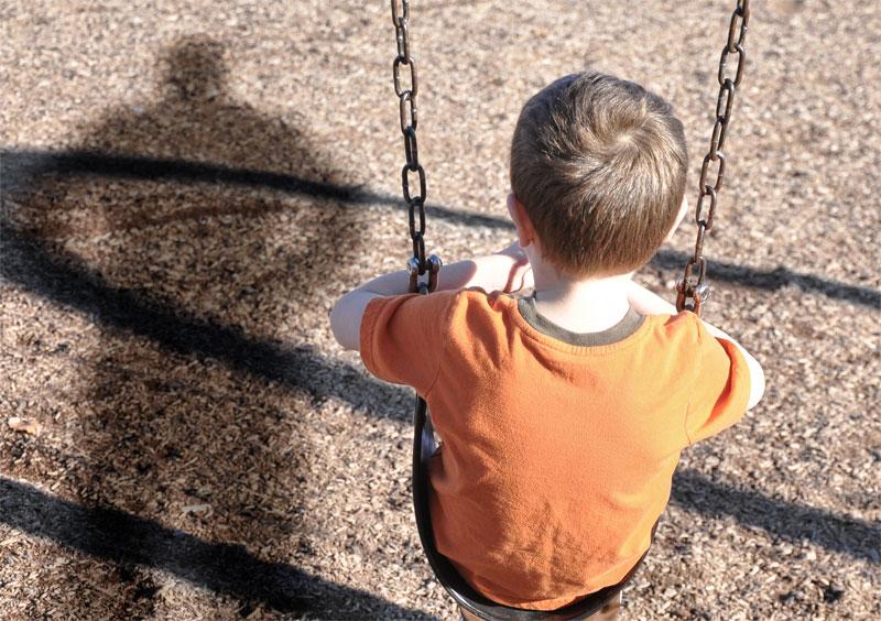 Einsames Kind sitzt auf einer Schaukel. Der drohende Schatten des Vaters hinter ihm.